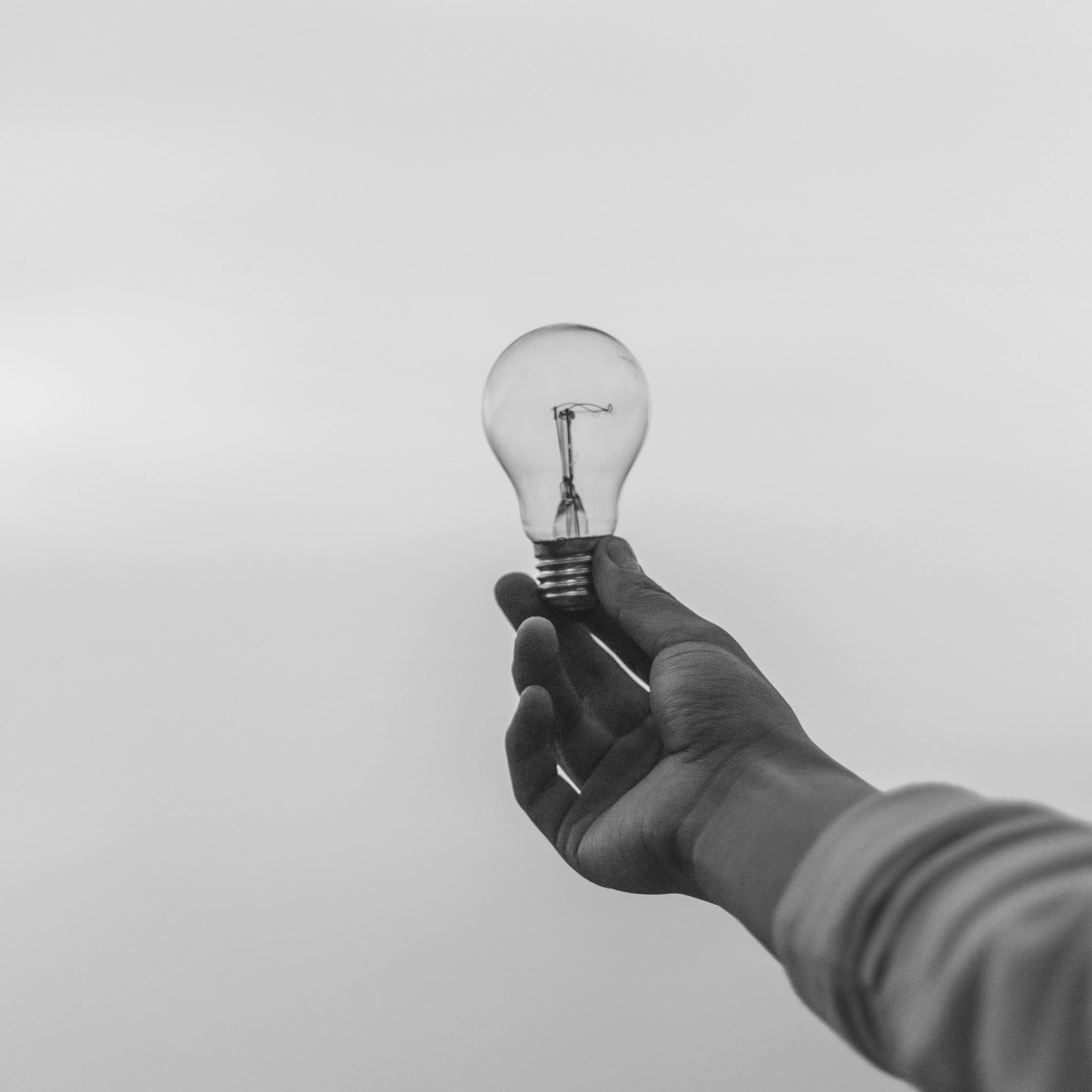 a hand holding a light bulb to the sky