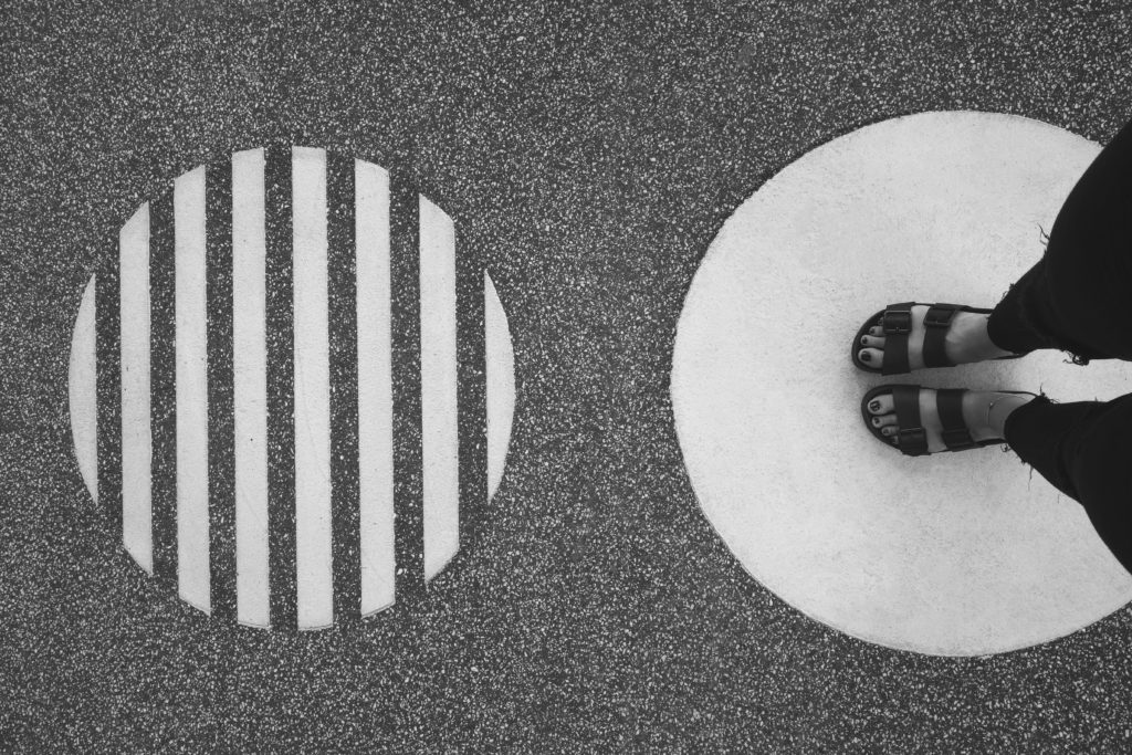 sandaled feet standing on a painted circle next to another painted circle with lines.
